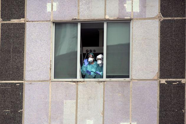 Dos sanitarios saludan desde el interior del Hospital de La Paz en