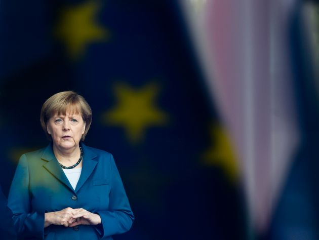 FILE - The June 3, 2013 file photo shows German Chancellor Angela Merkel stand behind a window with a...
