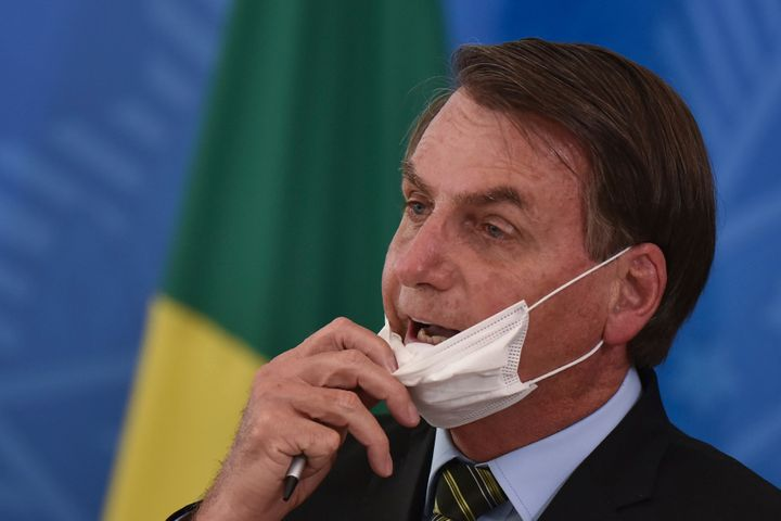 Brazil's President Jair Bolsonaro removes his mask to speak to journalists after a March 18 press conference on the new coron