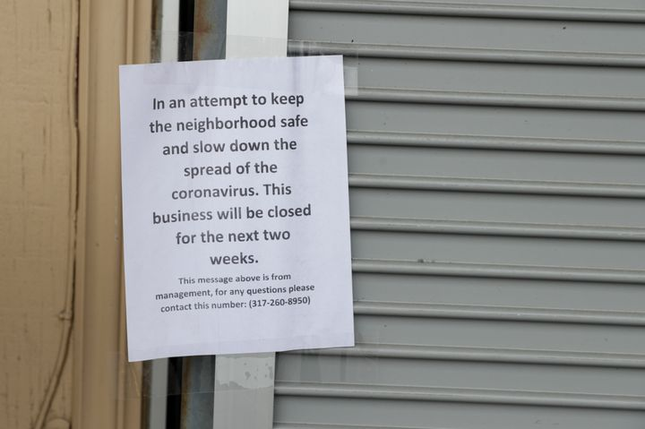 A sign on an Indianapolis liquor store announces its closure due to the coronavirus on March 28, 2020.