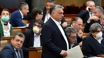 Hungarian Prime Minister Viktor Orban (C) walks near other representatives during a vote about the government's bill on the protection against the new coronavirus COVID-19 at the plenary session of the Hungarian Parliament in Budapest, Hungary on March 30, 2020. (Photo by Zoltan MATHE / POOL / AFP) (Photo by ZOLTAN MATHE/POOL/AFP via Getty Images)