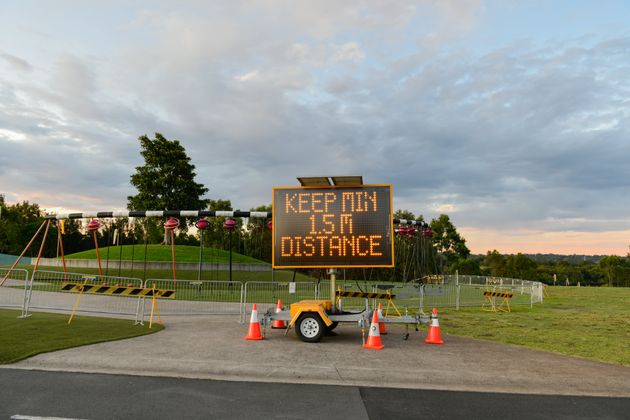 An information signboard 'Keep min 15m distance' is seen at outdoor playground at Sydney Olympic Park...