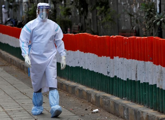 A health worker wearing a protective suit walks after moving people to a quarantine facility, amid concerns...