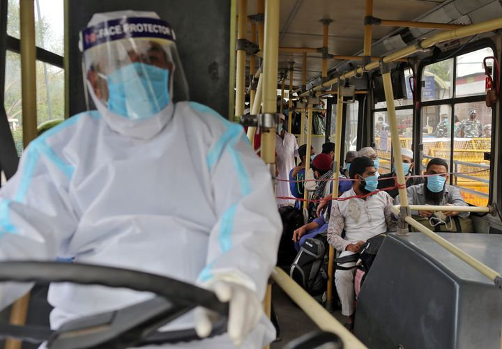 Men wearing protective masks sit inside a bus that will take them to a quarantine facility, amid concerns about the spread of coronavirus disease (COVID-19), in Nizamuddin area of New Delhi, India, March 30, 2020.