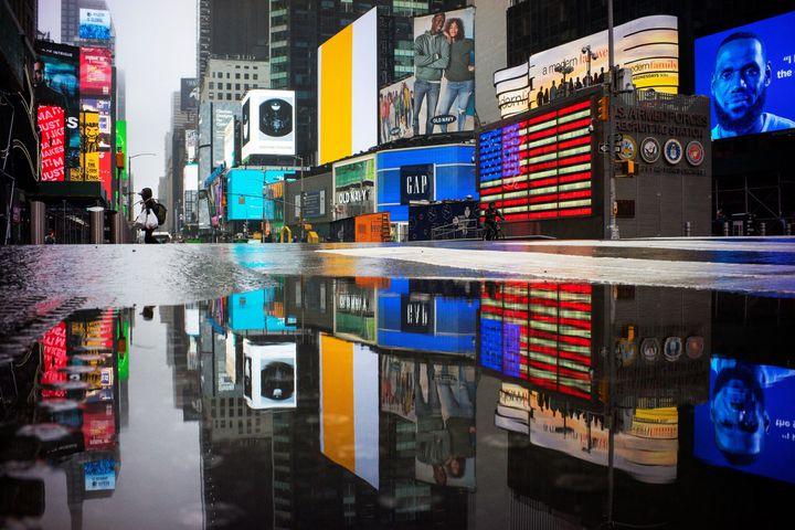 Homem atravessa a 7th Avenue em uma vazia Times Square, símbolo do consumo em Nova York. Avanço do coronavírus mantém as pessoas isoladas em casa.