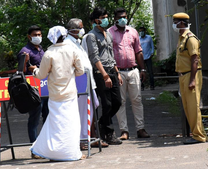 People are seen wearing masks outside the special isolation ward set up to provide treatment to novel coronavirus patients in Kerala, March 9, 2020.