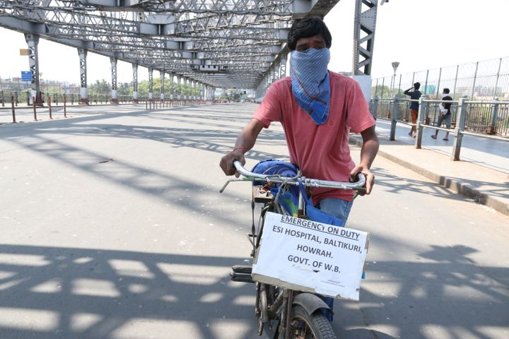 A ESI Hospital worker cycles on a deserted Howrah Bridge during the government-imposed nationwide lockdown in Kolkata on March 30,2020.