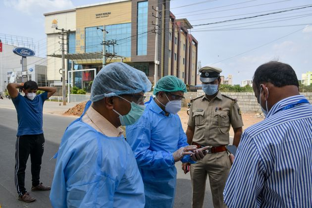 Paramedics, government municipal and police officials stand outside a private hotel in Bangalore on March...