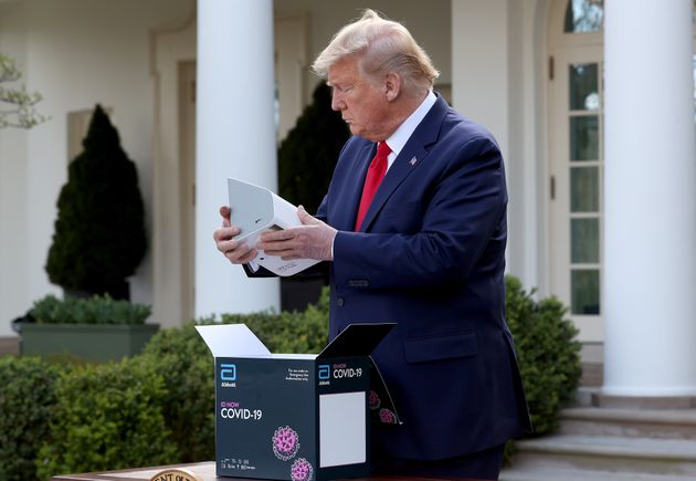 US President Donald Trump holds a new COVID-19 test kit developed by Abbott Labs during the daily coronavirus...