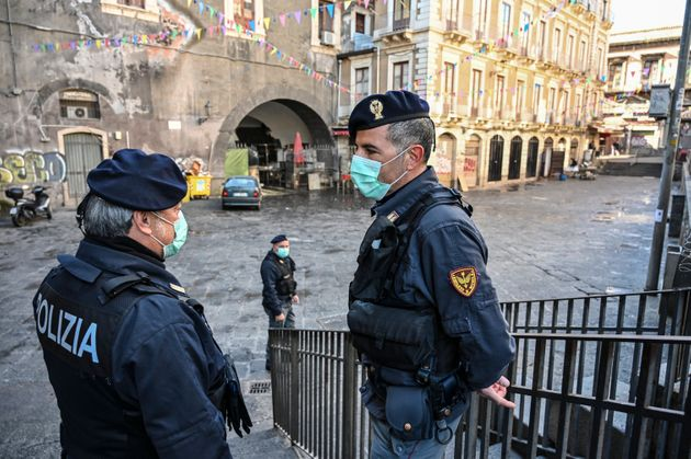 Police with the protective masks control the traditional open-air fish market in Catania, Italy, on March...