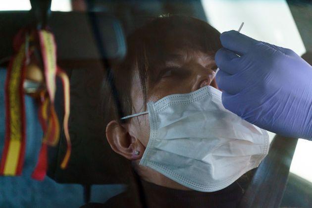Un sanitario toma muestras para una prueba de coronavirus en el coche de una paciente junto al Hospital...
