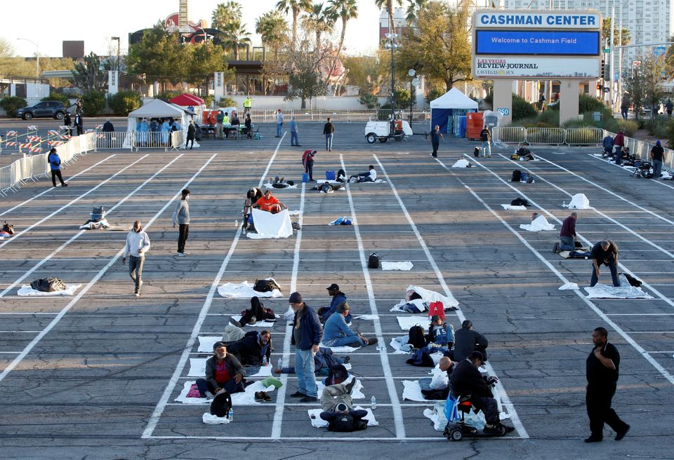 Homeless people get settled in a temporary parking lot shelter at Cashman Center, with spaces marked...