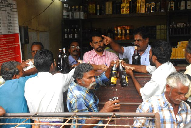 Customers buying alcohol from a shop run by Kerala State Beverages Corporation (KSBC) on Onam Day in