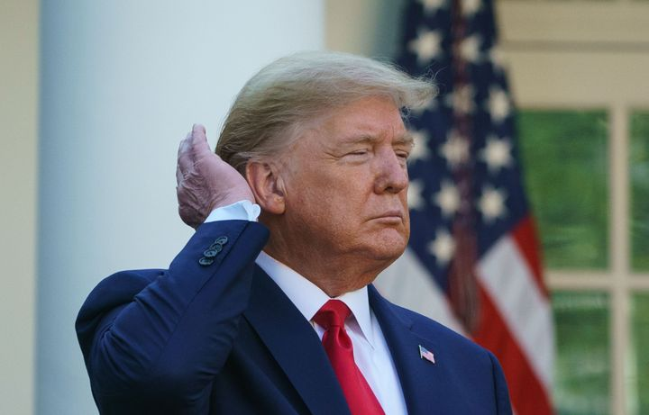 President Donald Trump pats down his hair as he speaks during the Coronavirus Task Force daily briefing on COVID-19 in the Rose Garden.