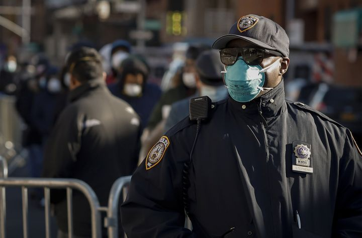 A New York City police officer wears protective gear while monitoring people waiting in line to be tested for the coronavirus