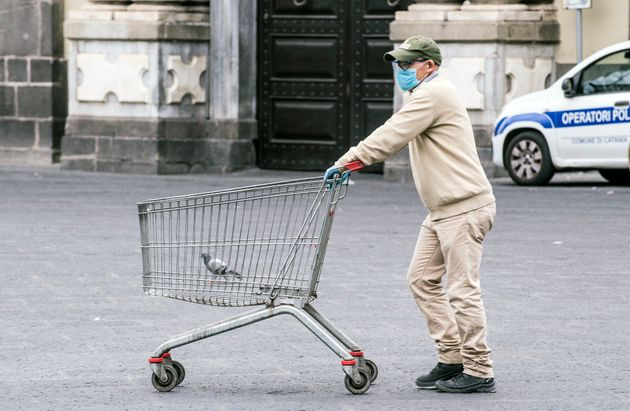 A man wearing a mask and gloves walks on an empty street in Catania, Italy, on March