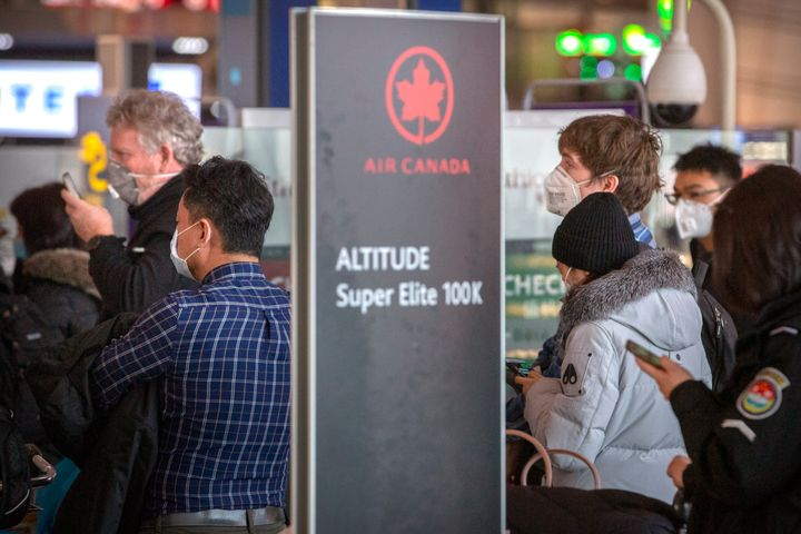 Travellers wearing face masks line up at the Air Canada check-in counters in Beijing on Jan. 30, 2020.