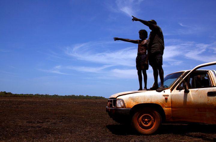 Australian Aboriginal hunters Bruce and Robert Gaykamangu look for potential prey at a billabong near the outstation of Ngangalala in East Arnhem Land.