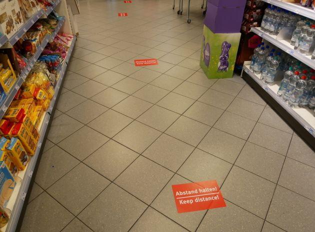スーパーのレジ前には待ち列の間隔をあけるための印が