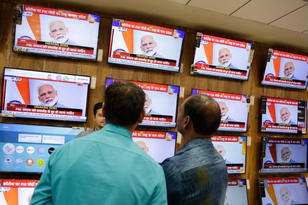 People watch Prime Minister Narendra Modi address the nation in a televised speech about COVID-19 situation,...