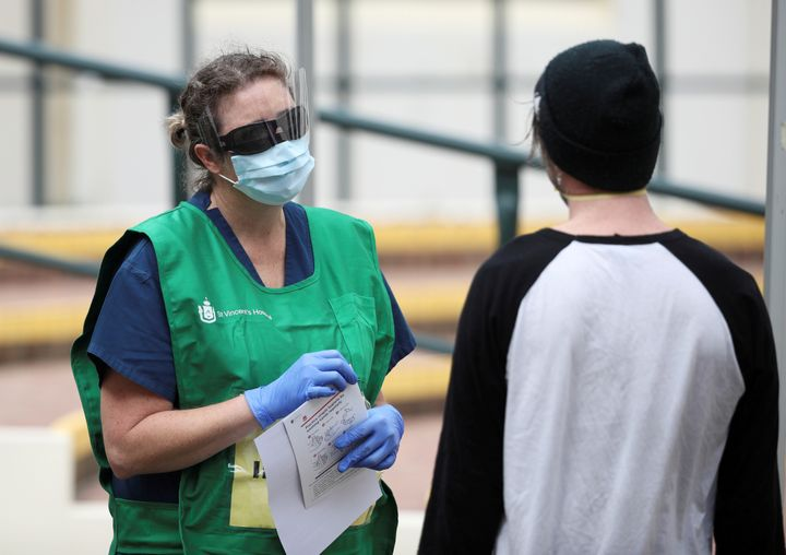 A healthcare professional talks to a man at a pop-up clinic testing for the coronavirus disease (COVID-19) at Bondi Beach, after several outbreaks were recorded in the area, in Sydney, Australia April 1, 2020.