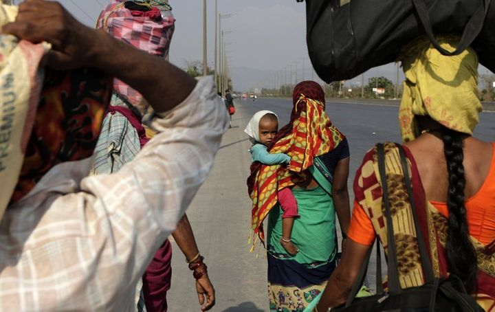 In this Sunday, March 29, 2020, photo, migrant workers walk to their villages along the Mumbai Pune highway during 2In this S