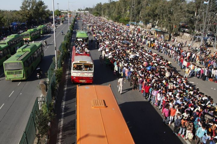 In this Saturday, March 28, 2020, photo, Indian migrant laborers wait for buses provided by the government to transport them