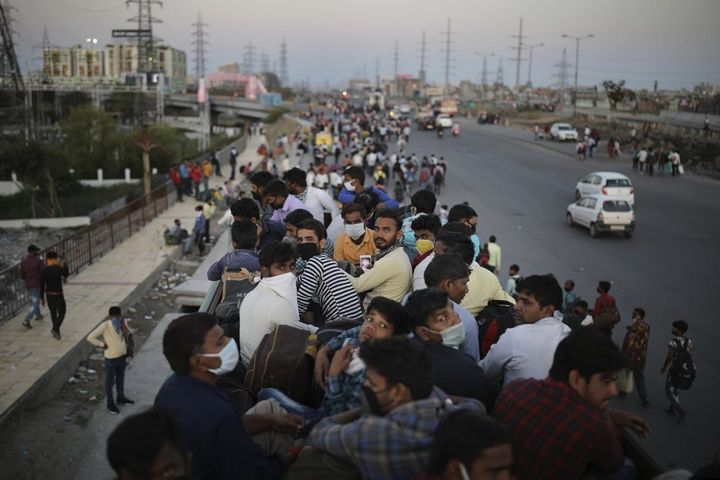 In this Saturday, March 28, 2020, photo, Indian migrant workers sit atop a bus, provided by the government, as others walk al