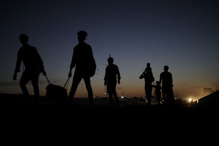 In this Saturday, March 28, 2020, photo, a migrant laborer's family is silhouetted as they proceed towards their village on f