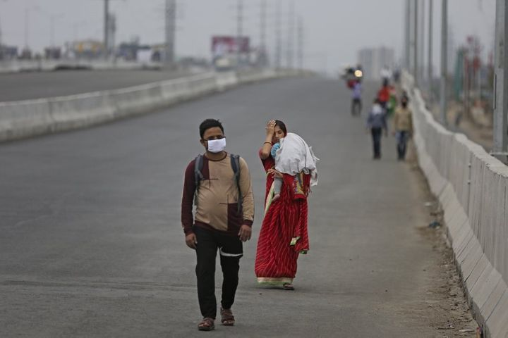 In this Thursday, March 26, 2020, photo, an Indian couple carrying an infant walk along an expressway hoping to reach their h