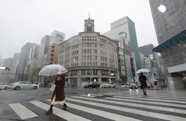 新型コロナウイルスによる外出自粛要請で閑散とした東京・銀座に舞う雪=3月29日