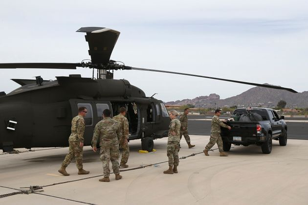 Members of an Arizona National Guard unit pause while loading a helicopter with medical supplies to be...