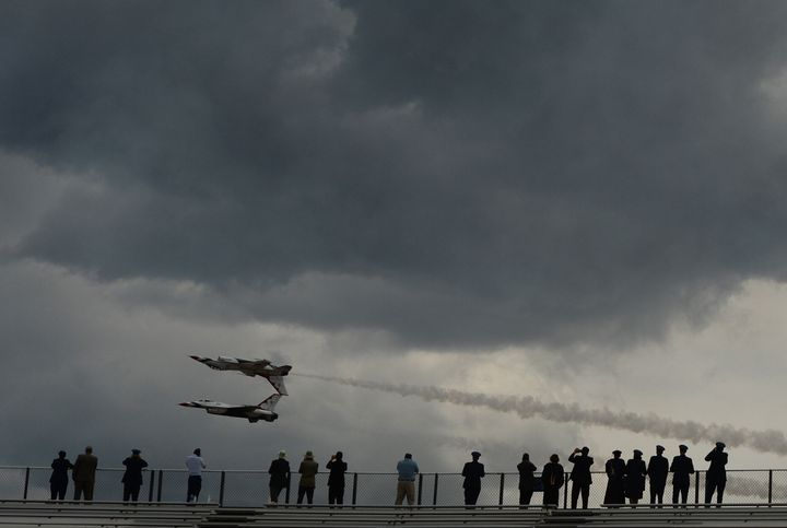 People watch an air show after graduation at the U.S. Air Force Academy in Colorado Springs. The academy said it will ease co