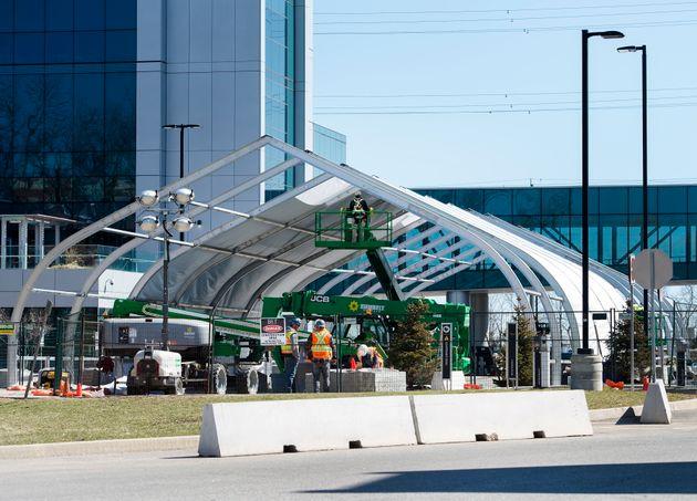 Construction workers help assemble a make-shift hospital outside the Joseph Brant Hospital in Burlington,...
