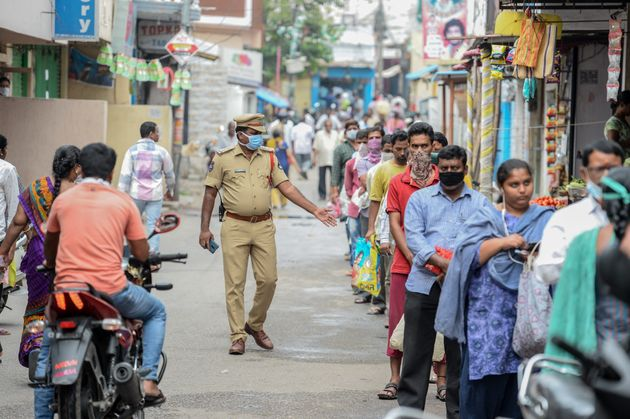 A policeman patrols as people queue to receive free rice distributed at a government civil supply store,...