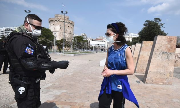 A policeman check a runner for valid documents during a lockdown order by the Greek government to control...