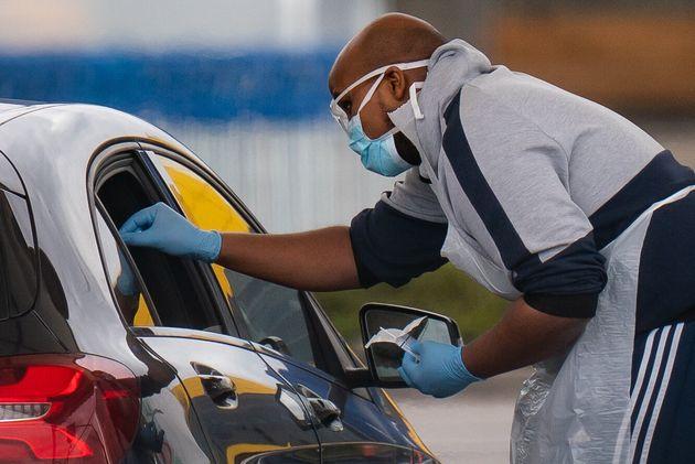 Medical staff at an NHS drive through coronavirus disease (COVID-19) testing facility in an IKEA car...