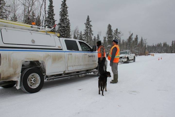 Security personnel stop an industry worker at a checkpoint set up at an entrance to the Waterhen Lake First Nation in Saskatchewan.