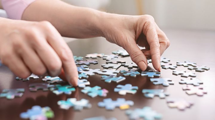 Dementia prevention. Elderly woman hands doing jigsaw puzzle at home, panorama, close up