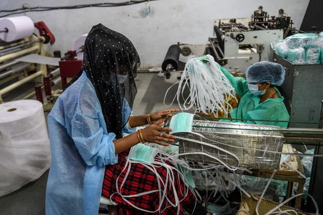 A worker collects facemasks from an assembly line at a facility of personal protective equipments manufacturer...