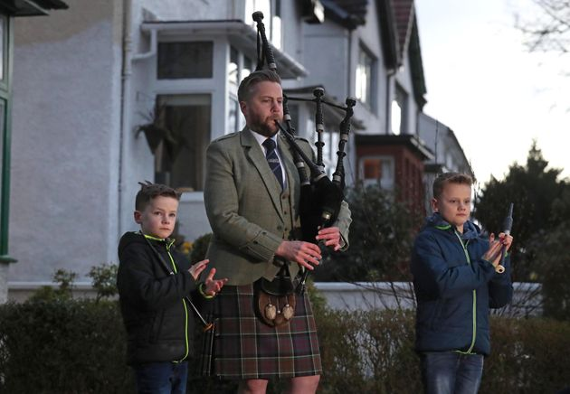 Finlay MacDonald plays the pipes at his home in Glasgow alongside sons Elliott, ten, and Fionn, eight,...