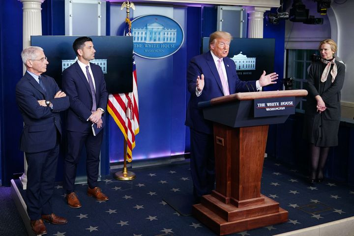 US President Donald Trump gestures as he speaks, flanked by Director of the National Institute of Allergy and Infectious Dise