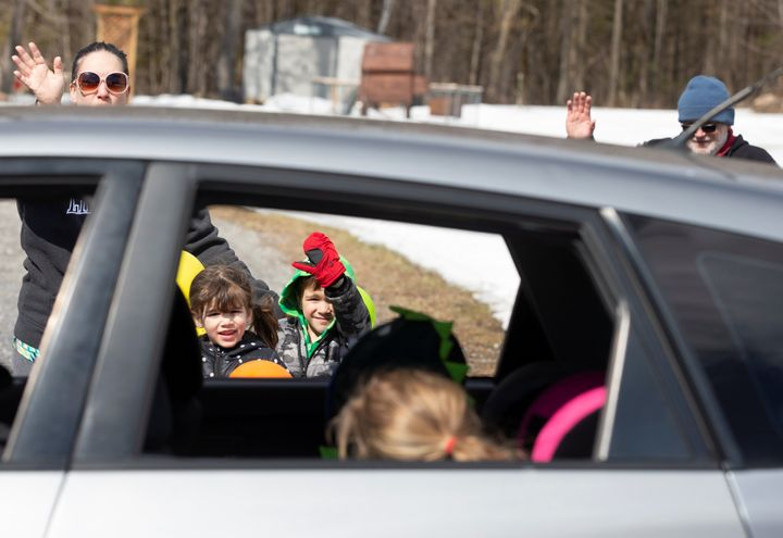 Charlotte and Calvin George wave with their parents as a car drives past their home to celebrate their fifth birthday while isolating amid the coronavirus outbreak in St-Eugene, Ont. on April 1, 2020.