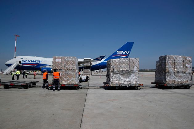 Workers unload a cargo plane at Eleftherios Venizelos International Airport in Athens on March 31. Scores...