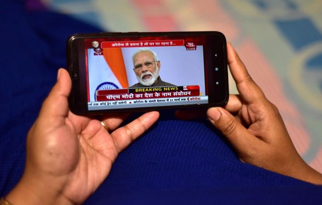 A person watches Prime Minister Narendra Modi address the nation in a televised speech about COVID-19...