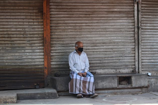 A man wearing a facemask sits outside closed shops during a government-imposed nationwide lockdown as...