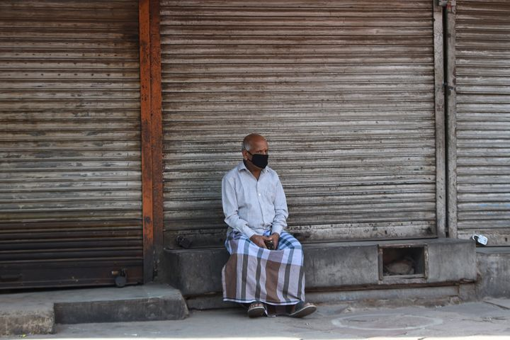A man wearing a facemask sits outside closed shops during a government-imposed nationwide lockdown as a preventative measure against the COVID-19 novel coronavirus in the old quarters of New Delhi on March 30, 2020.