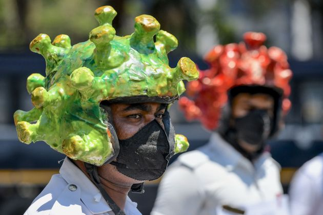 Traffic police personnel wearing coronavirus-themed helmets participate in a campaign to educate the...