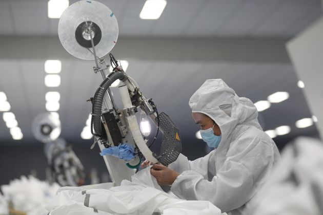 An employee works on a production line manufacturing protective suits at a medical supply factory in...