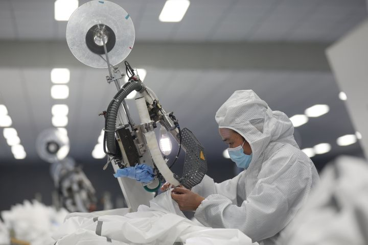 An employee works on a production line manufacturing protective suits at a medical supply factory in Xinzhou district of Wuhan, China February 12, 2020.